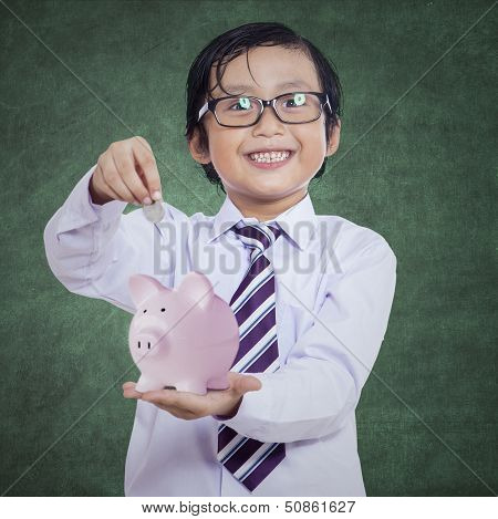 Happy Boy Puts The Coin Into A Piggy Bank