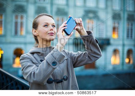 Elegant, young woman taking a photo with her cell phone camera while traveling (shallow DOF; color toned image)