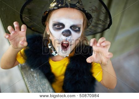 Portrait of cute girl in Halloween costume looking at camera with frightening expression