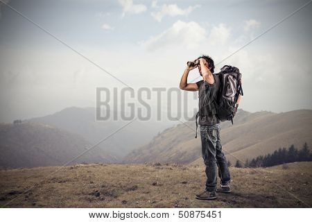 young man looking with binoculars in the mountains