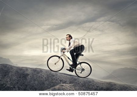 businessman cycling with fatigue in the high mountains