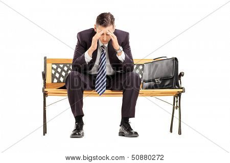 Disappointed young businessperson sitting on a wooden bench isolated against white background
