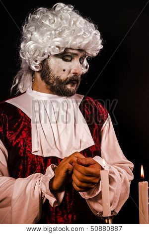 Rococo man. Young in eighteenth century image posing with candle
