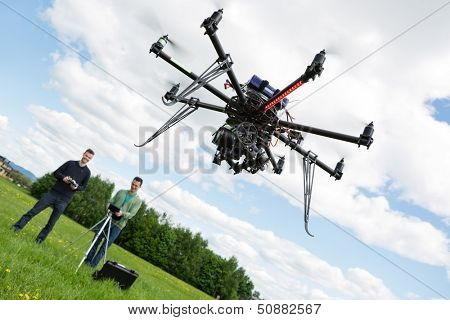UAV helicopter flying while male technicians operating it in park
