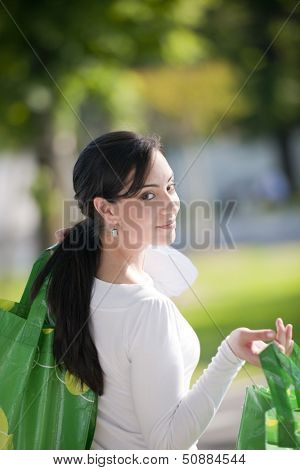 Beautiful young woman with reusable bags