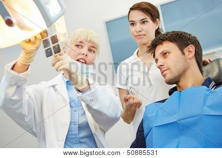 Female dentist showing caries on x-ray image to a patient before treatment