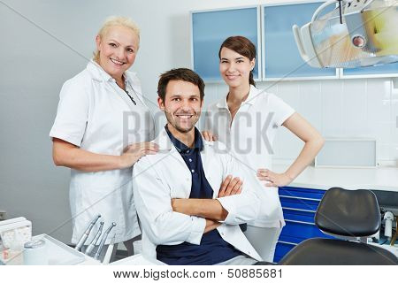 Happy group of employees at dentist with two dental assistants