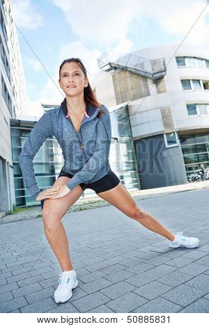 Atheltic woman doing stretching exercise for warm-up in the city