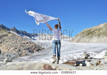 Girl holding a flapping shawl against Rhone glacier. Switzerland