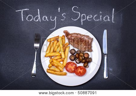 Steak and chips dinner on a chalkboard as the dish of the day.