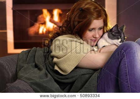Red hair teenager girl fondling cat at home sitting by fireplace.