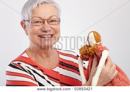 Grandmother holding rag doll, smiling, looking at camera.