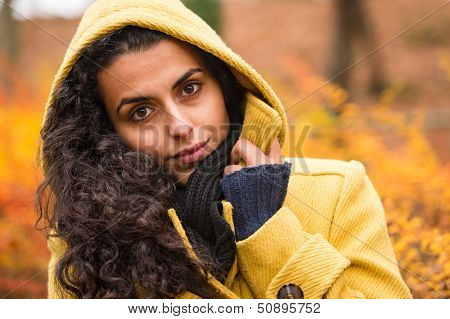 Woman looking at camera in hooded coat in fall forest
