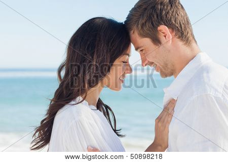 Romantic couple relaxing and embracing on the beach during the summer