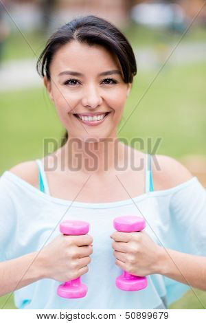 Happy woman exercising outdoors with free weights