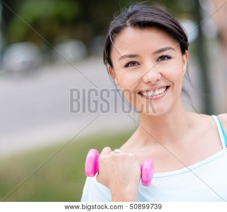 Happy fit woman training outdoors with free-weights