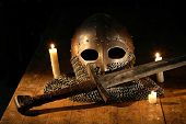 foto of medieval  - Medieval knight sword and helmet near lighting candles - JPG