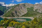 image of swales  - Wonderful mountain lake with high coast and beautiful island in the middle in Kyrgyzstan - JPG
