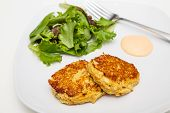 foto of crab-cakes  - Fresh crab cakes on a white plate with sauce and a salad of field greens - JPG