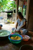 People make  Cylindric glutinous rice cake (banh tet) for Tet