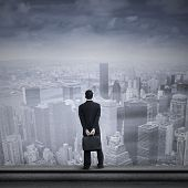 stock photo of filipino  - Portrait of a businessman looking into the future standing on the top of a skyscraper - JPG