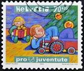 A stamp printed in Switzerland shows two children playing with the presents under the Christmas tree