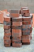 stock photo of xeriscape  - Stack of red charcoal colored bricks stacked and ready to construct - JPG