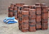 foto of xeriscape  - Stack of red charcoal colored bricks and bags of paving sand stack and ready for construction in desert environment