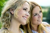 stock photo of identical twin girls  - Portrait of young Adult Sisters at the park