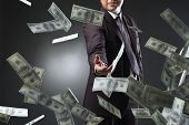 stock photo of corruption  - Handsome young man throwing money over dark background - JPG