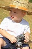 stock photo of baby cowboy  - a cute baby boy wearing a straw hat is sitting outside playing with a vintage camera - JPG