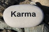 image of reinforcing  - Positive reinforcement word Karma engrained in a rock - JPG