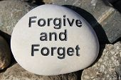 stock photo of reinforcing  - Positive reinforcement words Forgive and Forget engrained in a rock - JPG