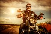 stock photo of biker  - Biker man wearing a leather jacket and sunglasses sitting on his motorcycle looking at the sunset - JPG