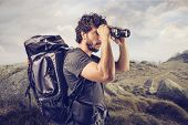 foto of binoculars  - young explorer in high mountain looks horizon with binoculars - JPG