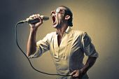 stock photo of singer  - successful singer singing with the microphone - JPG