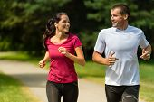 stock photo of spare  - Portrait of cheerful Caucasian couple running outdoors - JPG