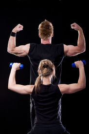 picture of fitness man body  - Fitness man and woman posing in gym showing their muscles isolated on black - JPG