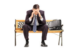 stock photo of disappointed  - Disappointed young businessperson sitting on a wooden bench isolated against white background - JPG