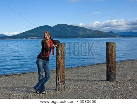 Teen Girl Leaning On Pole At Beach