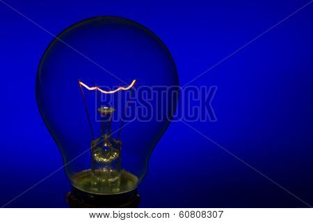 Glass Light Bulb With Burning Filament Upright With Blue Background