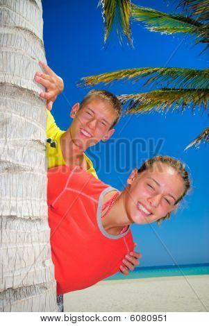 Siblings behind palm tree