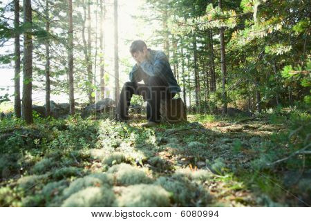 Sad Young Man Sits In Wood On Stone