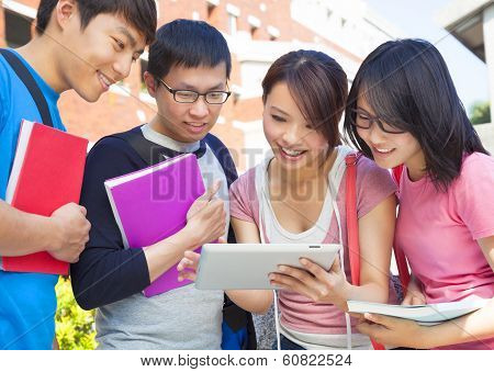 Group Of Students Discussing Homework By Using Tablet
