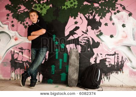 Young Boy With Shoulder Bag Agaisnt Purple Graffity Wall