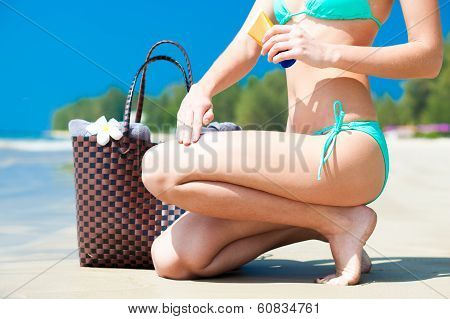 Suntan lotion and sunscreen. Woman applying sunblock cream on leg on tropical beach with beachbag