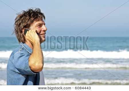 Young guy making a phone call at the atlantic ocean