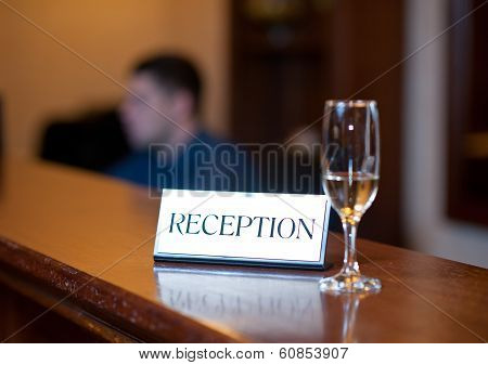 Reception card and champagne glass isolated on wooden table. Reception desk with card and glass