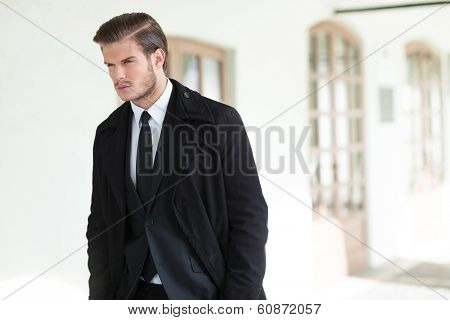 elegant young business man posing outdoor with his hands in his pockets and looking away from the camera