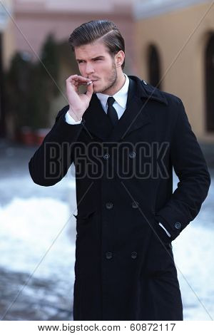 young business man smoking outdoor while holding a hand in his overcoat pocket and looking away from the camera